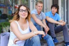 Jóvenes tres amigos que sientan el piso en la calle, hablando, con Imagen de archivo