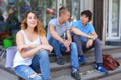 Jóvenes tres amigos que sientan el piso en la calle, hablando, con Imágenes de archivo libres de regalías