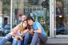 Jóvenes tres amigos que sientan el piso en la calle, hablando, con Imagenes de archivo