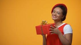 Júbilo divertido de la mujer, bailando con el presente recibido, fondo amarillo aislado almacen de video