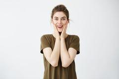 Júbilo feliz alegre joven de la muchacha que sonríe con las manos en las mejillas que miran la cámara sobre el fondo blanco Foto de archivo