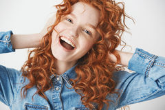 Júbilo sonriente de la muchacha alegre feliz del pelirrojo que mira la cámara con la boca abierta sobre el fondo blanco Foto de archivo libre de regalías