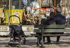 Júntese cerca del carrusel que se sienta en el banco que espera un carrusel de los paseos del niño imagenes de archivo