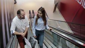Júntese con los paquetes en la escalera móvil Tema de las compras almacen de metraje de vídeo