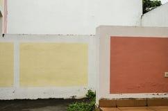 Júntese de dos paredes del cemento pintó blanco y adornado con los cuadrados amarillos y rojos, fondo de un día nublado fotografía de archivo libre de regalías