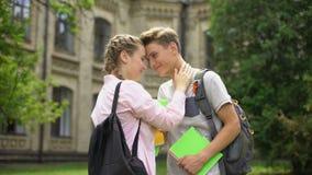 Júntese de estudiantes en el amor que abraza y nuzzling antes de las clases, vida de la universidad metrajes