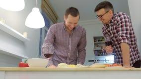 Júntese de hombres que el gay se liga que cocina una pizza junta y que bebe un vino metrajes