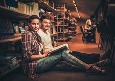 Júntese de los estudiantes que estudian en la biblioteca de universidad fotos de archivo libres de regalías