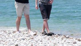 Júntese de los muchachos que caminan cerca del mar Mediterráneo claro en la playa blanca de la piedra de la arena almacen de video