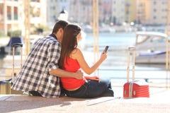Júntese de los turistas que comprueban el teléfono celular de vacaciones imagenes de archivo