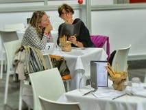 Júntese de mujeres elige del asiento del menú en el restaurante fotos de archivo