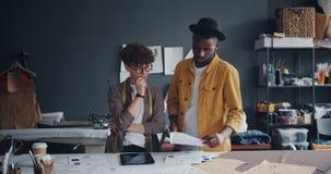 Júntese de sastres usando la tableta que mira los papeles que trabajan en taller junto almacen de metraje de vídeo