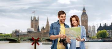 Júntese de turistas con el mapa y la cámara en Londres imágenes de archivo libres de regalías