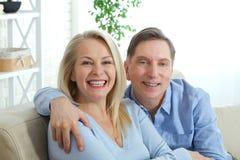 Júntese en casa en el sofá que habla y que sonríe foto de archivo libre de regalías
