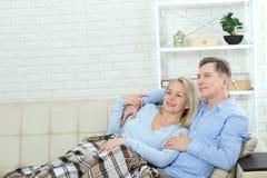 Júntese en casa en el sofá que habla y que sonríe imagenes de archivo
