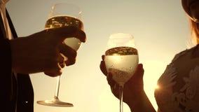 Júntese en el amor que sostiene las copas de vino con el vino espumoso en el fondo de la puesta del sol primer Trabajo en equipo  metrajes