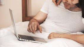 Júntese usando el ordenador portátil en cama almacen de video