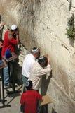 Jüdische Männer beten an der westlichen Wand, überwacht von einem jungen Jungen. Stockbild