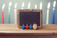Jüdischer Feiertags-Chanukka-Hintergrund mit hölzernem dreidel Kreisel und Tafel über Kerzen Lizenzfreies Stockfoto