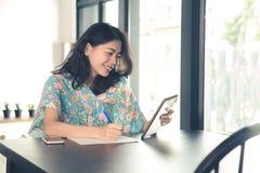 Jüngere asiatische freiberuflich tätige Frau, die zum Computertablettenschirm schaut Stockbild