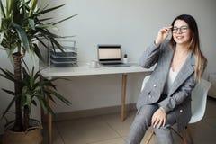 Jüngeres Mädchen, das im Büro am Tisch arbeitet stockfotos