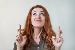 Język ciała Zabobonna caucasian kobieta z imbirowym włosy i ładnym twarzy skrzyżowaniem dotyka na dobre szczęście Fotografia Stock