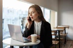 J'ai trouvé votre nombre en ligne et veux faire la réservation Tir d'intérieur de femme attirante occupée en café, regardant l'éc photographie stock
