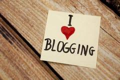 J'aime blogging avec la note stiky blanche sur un fond en bois Image libre de droits