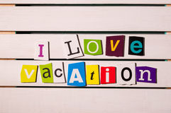 J'aime des vacances - écrites avec des coupures de lettre de magazine de couleur sur le conseil en bois Image de concept de voyag Images stock