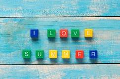 J'AIME L'ÉTÉ écrit dans les blocs en bois colorés sur un dos en bois Photos libres de droits