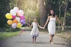 J'aime la maman reste ensemble le jour de mères Fille mignonne adorable tenant des ballons avec la mère image stock