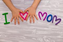 J'aime le texte de maman de la pâte à modeler avec des mains d'enfant sur le fond en bois blanc Jour de mères heureux Métier fait image libre de droits