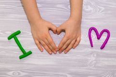 J'aime le texte de maman de la pâte à modeler avec des mains d'enfant sur le fond en bois blanc Jour de mères heureux Métier fait image stock