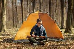 J?ger mit einem Gewehr im Wald, der nahe dem Zelt sitzt stockfotografie