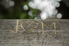 J and M letter - love symbol engraving. Heart scratched into a park bench Stock Photo