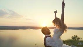J?ntese en la playa en puesta del sol La muchacha salta en sus brazos del novio C?mara lenta metrajes