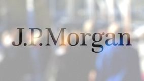 J.P. Morgan logo on a glass against blurred crowd on the steet. Editorial 3D rendering Stock Images