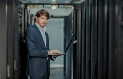 J?venes ?l hombre de negocios del ingeniero con el ordenador port?til de aluminio moderno fino en sitio de servidor de red foto de archivo
