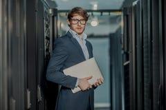 J?venes ?l hombre de negocios del ingeniero con el ordenador port?til de aluminio moderno fino en sitio de servidor de red foto de archivo libre de regalías