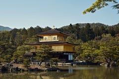 Jaśni niebieskie nieba przy Kinkaku-Ji świątynią otaczającą lasem zdjęcia stock