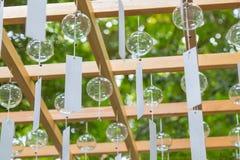 Jaśni szklani wiatrowi kuranty wieszają od drewnianej struktury podczas Wiatrowego Chi fotografia royalty free