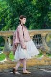 Jaźni ufna dziewczyna z wewnątrz białą skórzaną kurtką i suknią zdjęcia stock