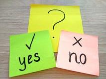 Ja eller inget frågemeddelande på klibbiga anmärkningar på trätabellbakgrund Problemlösning och valbegrepp arkivbild