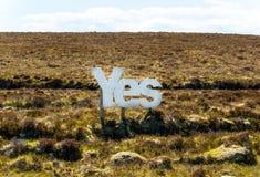 Ja in grote witte houten brieven met Schotse heide op de achtergrond Stock Foto