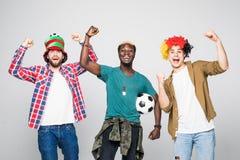 ja vinnarear Tre gladlynta unga män är stå och göra en gest för segern på vit bakgrund i tillfällig dräkt och jeans arkivbilder