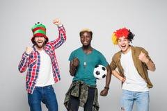 ja vinnarear Tre gladlynta unga män är stå och göra en gest för segern på vit bakgrund i tillfällig dräkt och jeans fotografering för bildbyråer