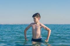 13 jaar de oude handen van de jongensholding op heupen en verbolgen status in de overzeese golven stock foto's