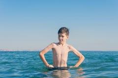 13 jaar de oude handen van de jongensholding op heupen en verbolgen status in de overzeese golven stock foto