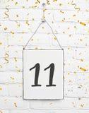 11 jaar de oude van de verjaardagspartij kaart met nummer elf met gouden Stock Afbeelding