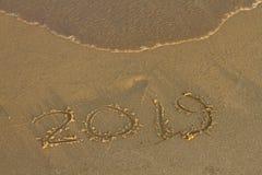 Jaar 2019 geschreven bij het zand op een overzees strand stock foto's